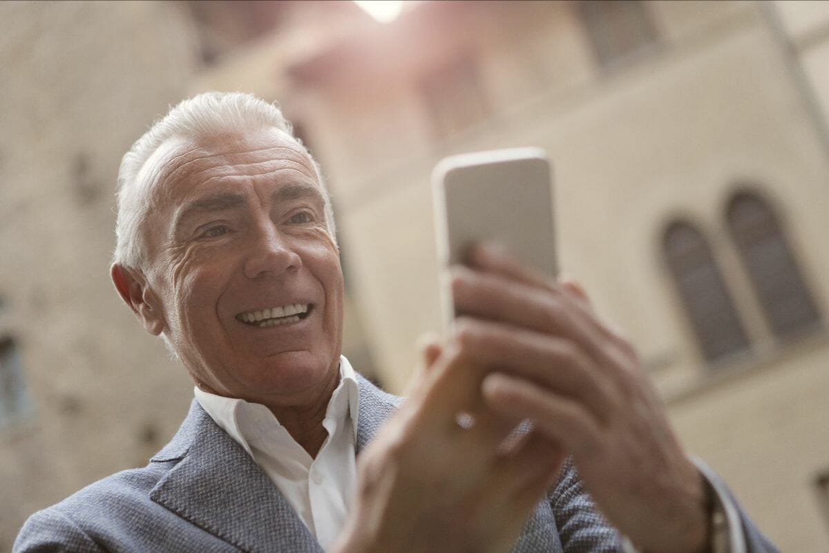 Business Thriving During a Crisis - Open Sign Small Business - Older Man Holding Cell Phone